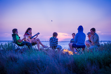 people sitting on the beach with campfire at sunset Fototapete