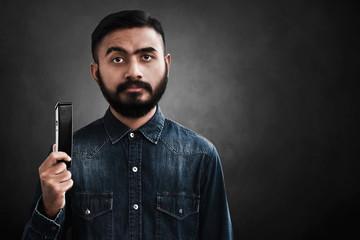 Portrait of handsome bearded man holding electric razor