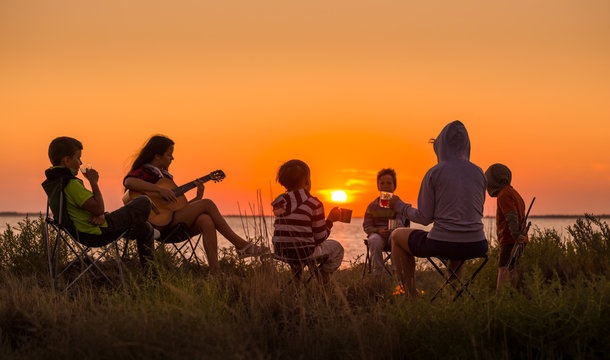people sitting on the beach with campfire at sunset