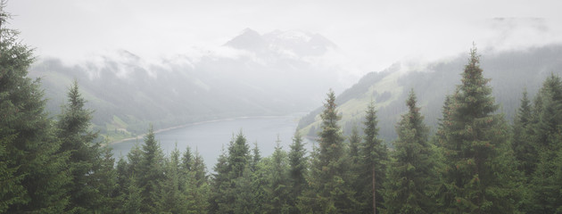 In de dag Khaki Panorama of a misty lake in the Alps with snow capped mountains. Mysterious scene.