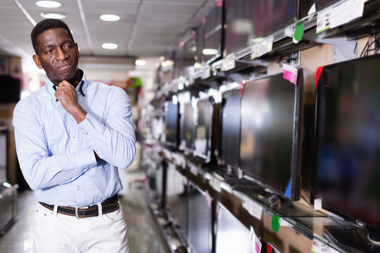 Positive man chooses TV set in store of household appliances