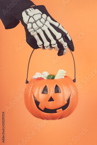 Happy Halloween.Child's hand in a skeleton glove with halloween pumpkin