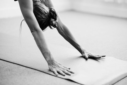 Classical black and white Art Photography of a woman practicing advanced yoga pose indoors on a yoga mat.  Woman's dynamic arms in Downward Dog.