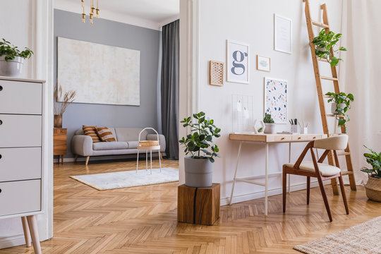Stylish and design home interior of open space with wooden desk, sofa, chair, cube, a lot of plants, mock up poster frames and elegant accessories. Classic and minimalistic home decor. Template.