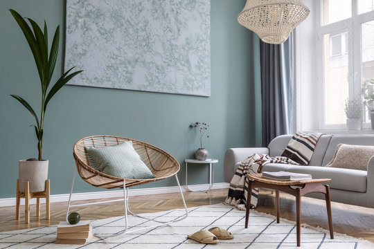 Bohointerior design of living room with sofa and rattan armchair