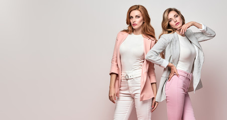 Wall Mural - Fashion. Two Beautiful woman in autumn stylish jacket, make up. Lovable sisters friends. Sensual glamour well dressed girl, long wavy hair.Creative fashionable portrait, beauty makeup autumnal concept