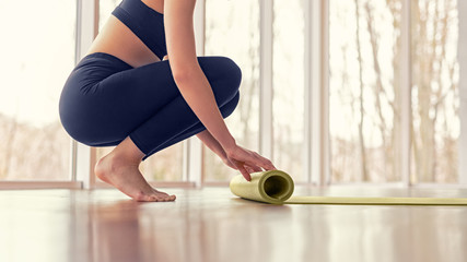 Crop female unrolling mat before yoga lesson Fototapete
