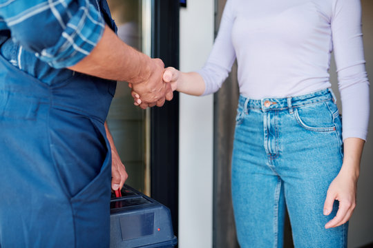 Young female client and repairman shaking hands after mechanic or technical work