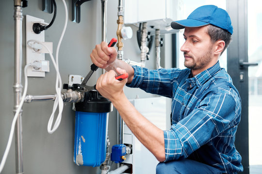 Young plumber or technician installing or repairing system of water filtration