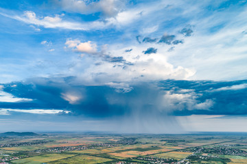 Beautiful rain cloud and rain over the fields. Aerial photography.