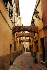 Three arches span a small pedestrian street in the old medieval borgo of Albenga, Liguria, Italy