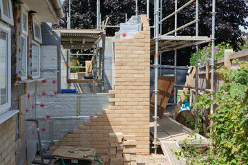 Renovation projects. Building of extension of the existing house, unfinished brick walls, block work, insulation, stacks of materials on scaffoliding, selective focus