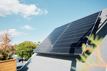 Obraz Large solar panels on rooftop of modern comfortable house or cottage - fototapety do salonu