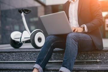 Crop businessman using laptop near gyroscooter