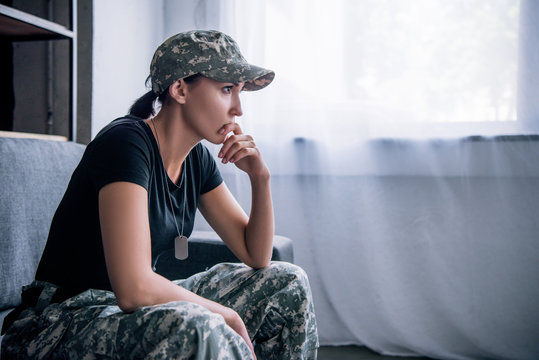 depressed lonely woman in military uniform at home