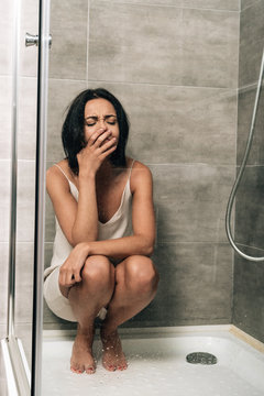 attractive depressed woman sitting and crying in shower at home