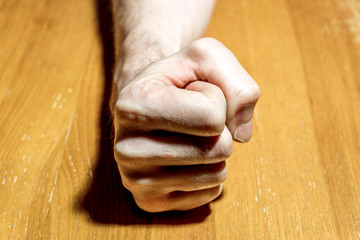 Man's hand clenched into a fist on the  table