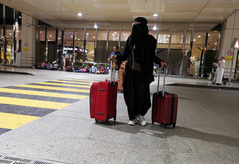 A Saudi woman walks with her luggage as she arrives at King Fahd International Airport in Dammam