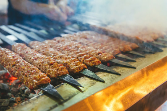 Traditional Turkish Adana Kebab or Kebap on the grill with skewers in the restaurant for dinner