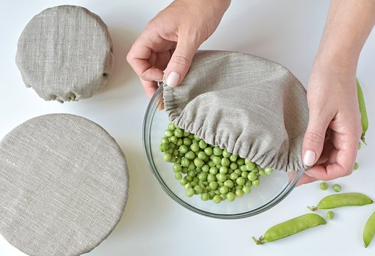 Linen reusable bowl covers, zero waste kitchen, top view, woman cover up bowl with peas