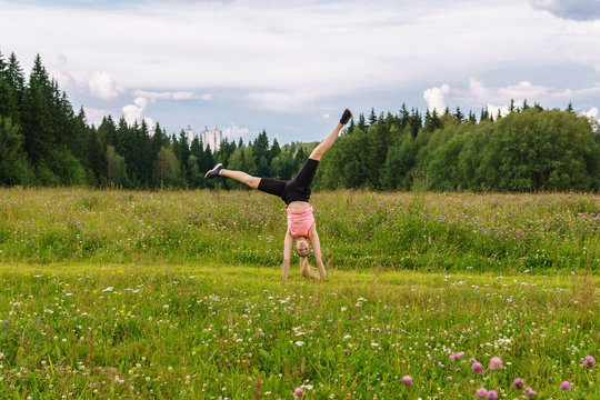 young woman doing exercises cartwheel in a meadow outside the city