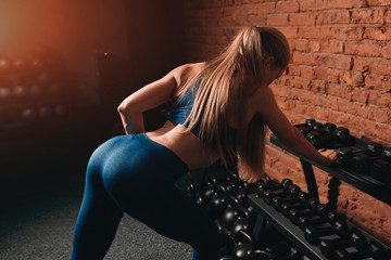 girl with sexy beautiful ass training in the fitness center. strong athletic woman working out with kettlebell weight.close up back view photo