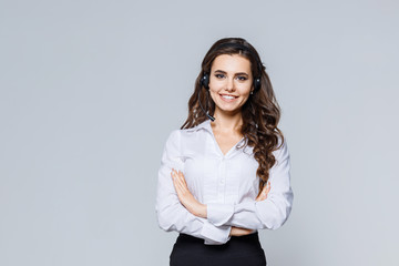 Young friendly operator woman agent with headsets standing near gray background. Call Center Service. Photo of customer support or sales agent in smart casual wear with crossed arms.