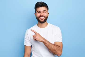 Young handsome charming man showing something with index finger, place for text, advert, copy space. isolated on blue background. direction. body language. sale, shop