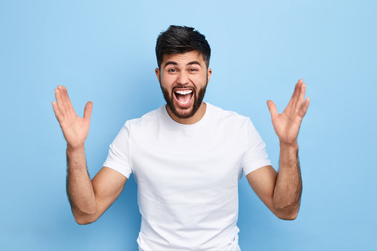 Cheerful handsome happy guy with wide opened mouth raising his hands up, having eyes full of happiness, rejoicing his achievements.