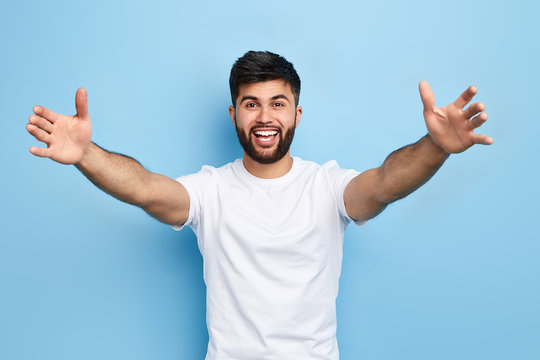 happy handsome Arab bearded young man standing with raised arms, he wants to hug his friend, isolated on blue background.. I love you. I miss you.body language