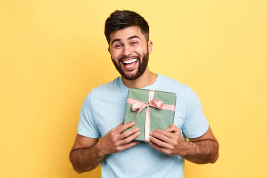 handsome bearded overjoyed man wearing casual clothes holding present box standing isolated over yellow background,Birthday party. celebration, happiness, best present from girlfriend