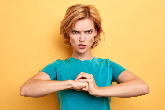 frustrated nervous woman worming up her fists before the fight, angry housewife waiting for her husband from work. close up portrait. workout, isolated yellow background