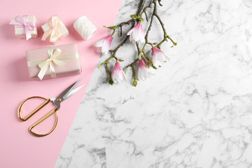 Flat lay composition with scissors, gifts and spring flowers on color background, space for text