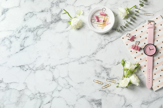 Flat lay composition with flowers, notebook and wristwatch on white marble background, space for text