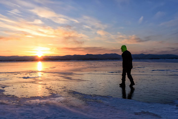 silhouette of man that are walking on the ice floor on the lake baikal with sunset.