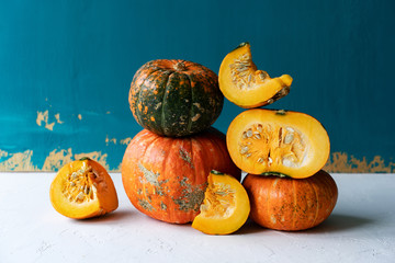 Slices of pumpkins and whole pumpkins on a bright blue background, simple vegetable still life.