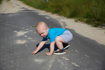 A boy gets up from an asphalt road after a fall, the theme of child injuries