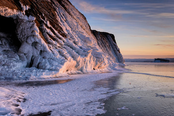 Lake Baikal is covered with ice and snow, strong cold, thick clear blue ice. Icicles hang from the rocks. Lake Baikal is a frosty winter day. Amazing place