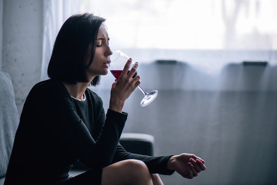 depressed lonely woman sitting on couch and drinking wine at home