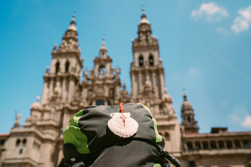 Pilgrim's backpack with famous pilgrims' mascot and sign seashell with Cross of Saint James at  on the Obradeiro square (plaza) - the main square in Santiago de Compostela with Catedral de Santiago. Fotomurales