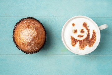 White cup of coffee with panda pattern on the foam and a cupcake on a blue wooden background, top view, copy space.