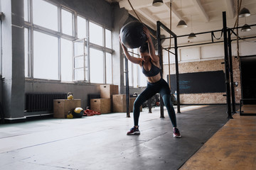 Woman doing exercise with heavy medicine ball in gym. Fototapete