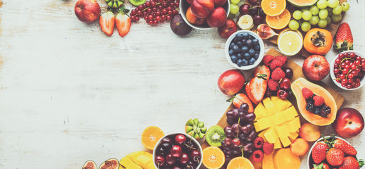 Wall Mural - Healthy raw fruits background, cut mango papaya, strawberries raspberries oranges plums apples kiwis grapes blueberries cherries, on white table, copy space, top view, toned, banner, selective focus