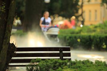 Ławka w parku, kobieta z wuzkiem i mgła, dziecko. Fototapete