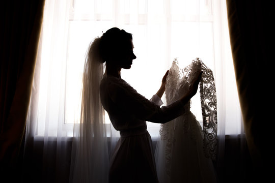 Bride holding white wedding dress with lace, embroidery. Bride getting ready