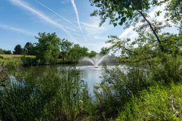 Water Fountain in Pond with Jet Contrails in Sky - Horizontal