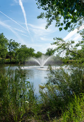 Water Fountain in Pond with Jet Contrails Across Sky - Vertical
