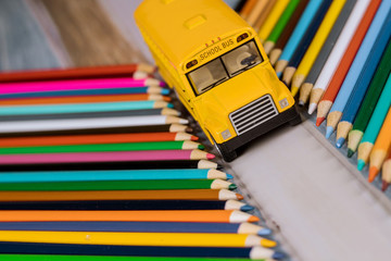 Yellow school bus toy with colored pencils
