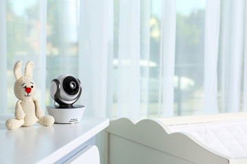 Baby camera with toy on chest of drawers in room, space for text. Video nanny
