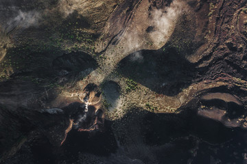 Aerial view of Batur volcano caldera in Bali. Volcanic black texture and crater rim, view from above, drone shot Wall mural